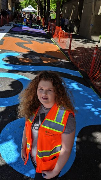 PAMPLIN MEDIA GROUP: JOSEPH GALLIVAN  - A junior in PSU's graphic design program Sadie Jordan, 21, adapted the pride rainbow for the street painting on to the asphalt.