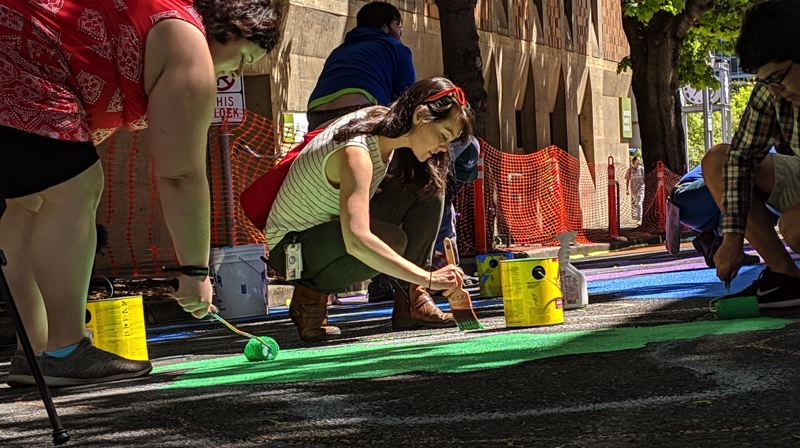 PAMPLIN MEDIA GROUP: JOSEPH GALLIVAN - Helpers fill in the lines of the pride-themed street painting at the new Montgomery Pop-Up Plaza at Portland State University on Wednesday May1, 2019. As an experiment the block will be closed to vehicular traffic in May and activated with student art and academic work.