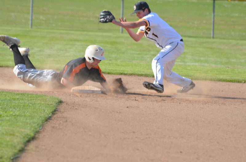 COURTESY PHOTO: JOHN BREWINGTON - Scappoose's Connor McNabb dives back to the bag during the visiting Indians' third and final Northwest Oregon Conference game this season against St. Helens.