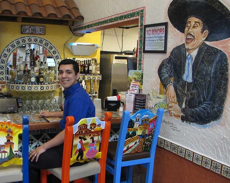 PMG PHOTOS: BILL GALLAGHER - Bryan Ochoa sits at the bar of Casa Colima in one of the dozens of chairs at the restaurant built and painted by hand by artisans in Guadalajara, Mexico.