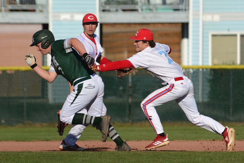 PMG PHOTO: DAVID BALL - Centennial shortstop Kyle Fitzgerald reaches out to tag Reynolds runner Drexler Dickey to end a rundown between second and third base.