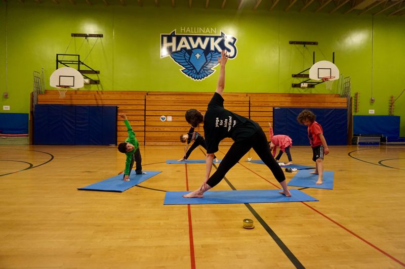PMG PHOTO: CLAIRE HOLLEY - Yoga for Kids founder Kathleen Peek takes Hallinan students through triangle pose during a recent yoga class.