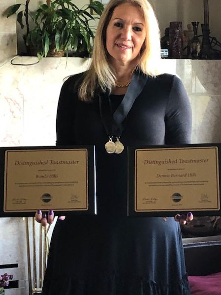 COURTESY PHOTO - Ronda Hill holds two plaques from Toastmasters International recognizing her and her late father, Dennis Hills, for earning the status of Distinguished Toastmaster after years of work and dedication to the goal.