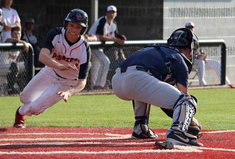 PMG PHOTO: JIM BESEDA - Oregon City's Ashton Stalheim dives for the plate as Lake Oswego catcher Gabe DeVille fields a low throw in the fourth inning of Thursday's Three Rivers League baseball game at Oregon City.