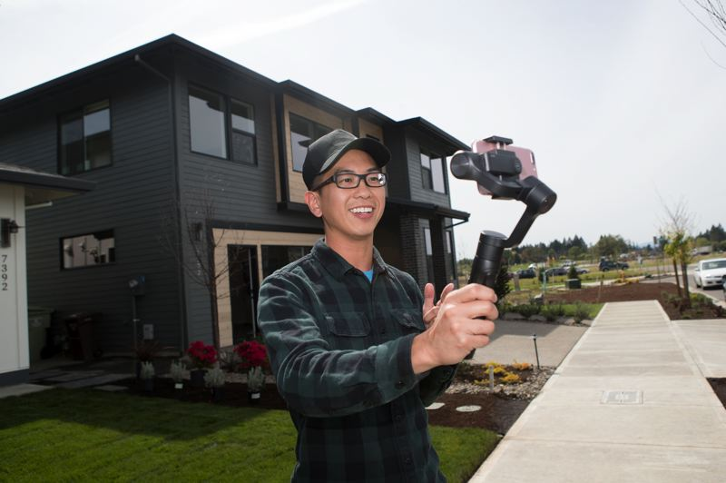 PAMPLIN MEDIA GROUP: JAIME VALDEZ - Real estate broker Alexander Pham uses a steady cam to shoot stills, video and commentary of the show homes at Reeds Crossing in South Hillsboro. Pham, who is from the area, likes selling brand new homes.