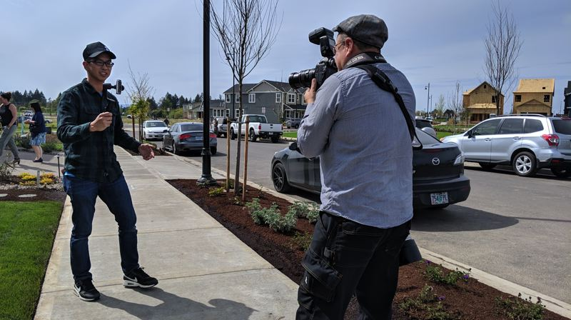 PAMPLIN MEDIA GROUP: JAIME VALDEZ - Tribune photographer Jaime Valdez (right) captures real estate broker Alexander Phan using a steady cam to shoot stills, video and commentary of the show homes at Reed's Crossing in South Hillsboro.