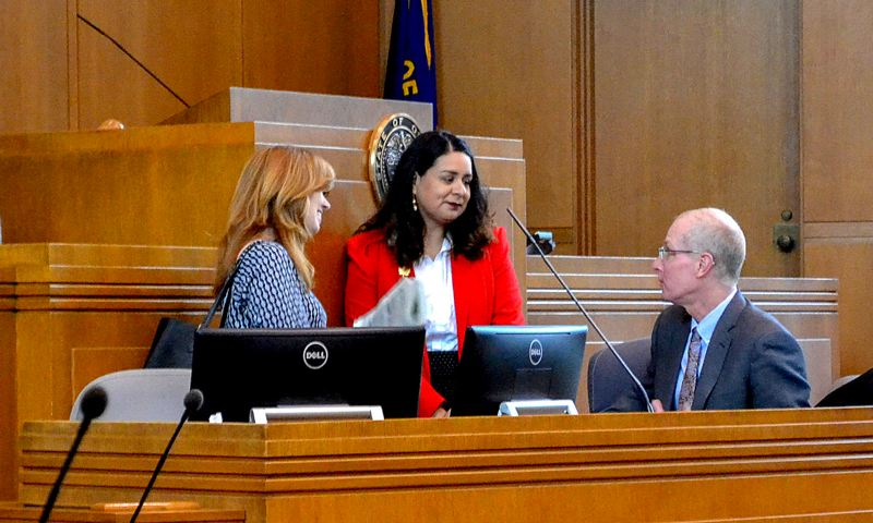 OREGON CAPITAL BUREAU: CLAIRE WITHYCOMBE - Lacy Ramirez Gruss, center, a reading clerk in the office of the Chief Clerk of the House, speaks to state Rep. Christine Drazan, R-Clackamas County, and Chief Clerk Tim Sekarak, on Thursday, May 2.
