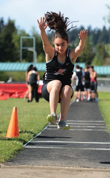 PMG PHOTO: DAVID BALL - Clackamas senior Erica Pasquantonio sails through the air during her second-place finish in the long jump Tuesday against Sandy.