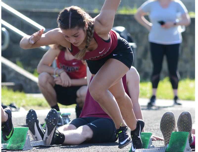PMG PHOTO: DAVID BALL - Sandy sprinter Marley Salveter comes out of the blocks during her win in the 100-meter dash.