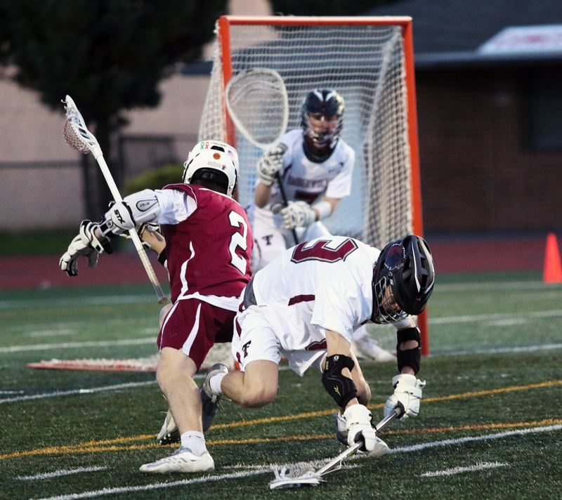 PMG PHOTO: DAN BROOD - Sherwood High School junior Brody Stevens (2) battles Tualatin junior Jeff Jost for the ball in front of Timberwolf goalie Alex Buelna.