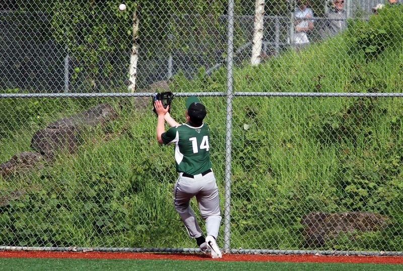 PMG PHOTO: MILES VANCE - Tigard right fielder Fletcher Ahl tries to make a running catch at the fence during his team's 4-2 loss at West Linn High School on Friday, May 3.