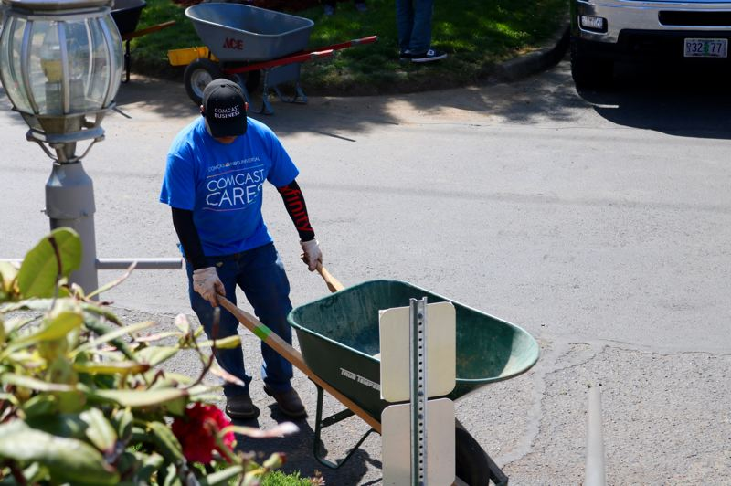 PMG PHOTO: ZANE SPARLING - A volunteer pushes a wheelbarrow during Comcast Cares Day on Saturday, May 4.
