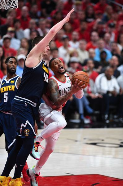 PMG PHOTO: CHRISTOPHER OERTELL - Damian Lillard of the Trail Blazers challenges Denver Nuggets center Nikola Jokic inside during Game 4 on Sunday at Moda Center.