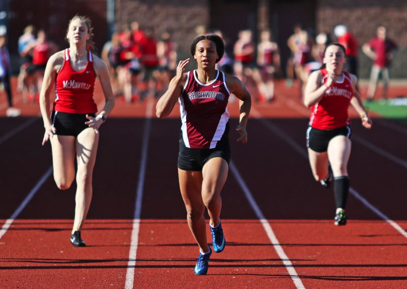 PMG PHOTO: DAN BROOD - Sherwood High School sophomore Nora Hagan (center) is on her way to victory in the 100-meter dash during the Lady Bowmen's Pacific Conference dual meet with McMinnville.