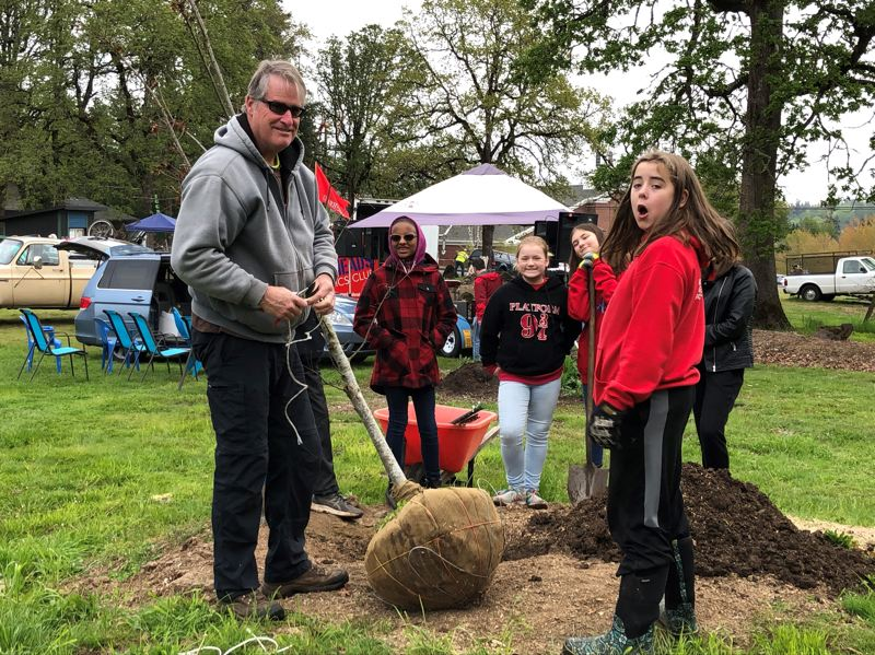 Kraxberger Gearheads club members, including Kellen Hirte (right) help excavate a large hole for an Oregon white oak, sourced by certified arborist Andrew Craig (left). The club previously helped recycle metal and clear trash in the park.