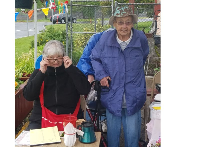 SUBMITTED PHOTO - Roberta Mills and Enid Briggs greet attendees at last year's Milwaukie GardenClub plant sale. Both women are past presidents of the club.