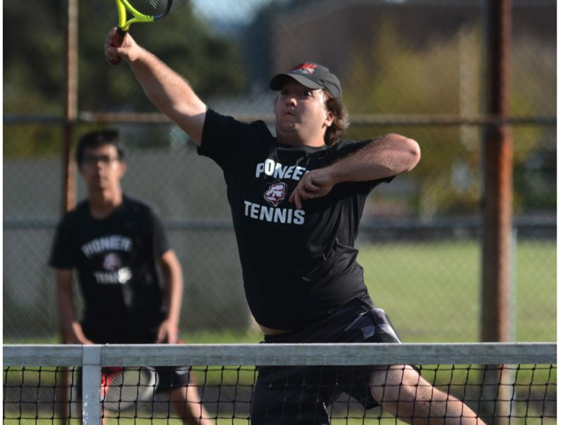PMG PHOTO: DAVID BALL - Sandys Josh Warner goes for a put-away shot at the net during a three-set win at No. 4 doubles along with partner Tri Nguyen (background) last week at Reynolds.