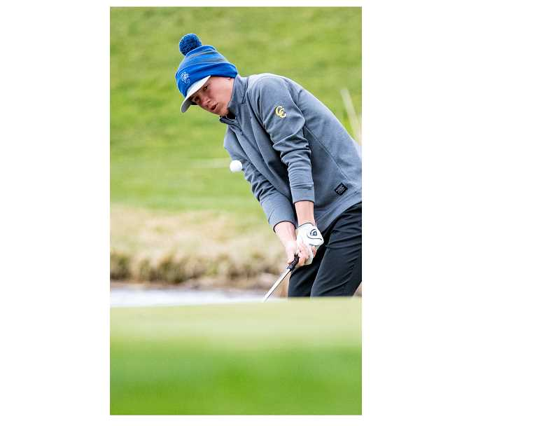 LON AUSTIN/CENTRAL OREGONIAN - Hogan Smith chips onto the green during a match earlier this year. Smith finished in third place Thursday as the Cowboys won the Sisters Invitational, which was held at the Glaze Meadows Course in Black Butte.