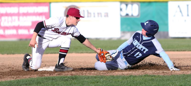 PMG PHOTO: DAN BROOD - Sherwood High School senior Christian Goyer tags out Liberty sophomore Grant Koons during the Bowmen's 10-0 conference victory.