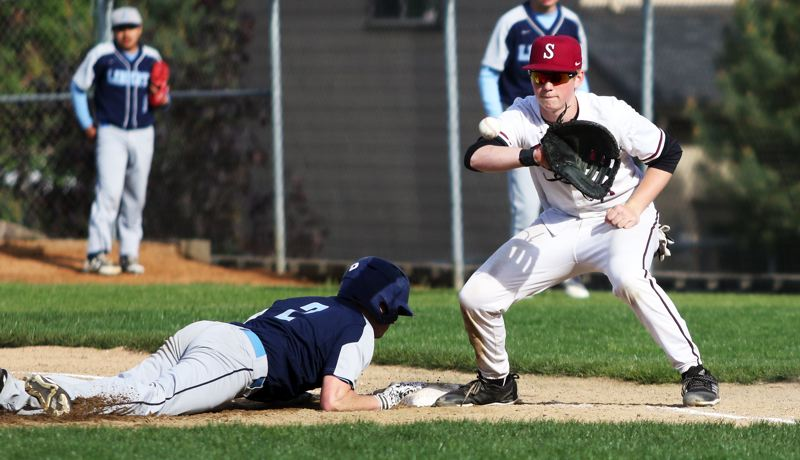 PMG PHOTO: DAN BROOD - Sherwood freshman first baseman Ian Umlandt looks to grab the ball as Liberty senior Joseph Depinto dives back to the base on a pickoff attempt in Friday's game.