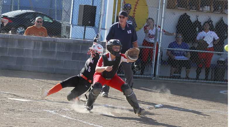 STEELE HAUGEN - Marrin McCleod, of Gladstone, slides home, while Madras' Hannah Holiday waits for the ball to arrive. The Gladiators beat Madras 5-4 in extra innings.