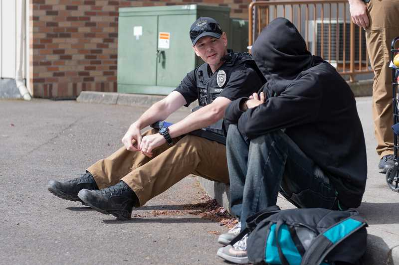 PMG PHOTO: CHRISTOPHER OERTELL - Mike Abshier, homeless liason officer with the Hillsboro Police, speaks to a homeless man at the St. Vincent de Paul food pantry in Hillsboro, Ore., on Thursday, May 2.