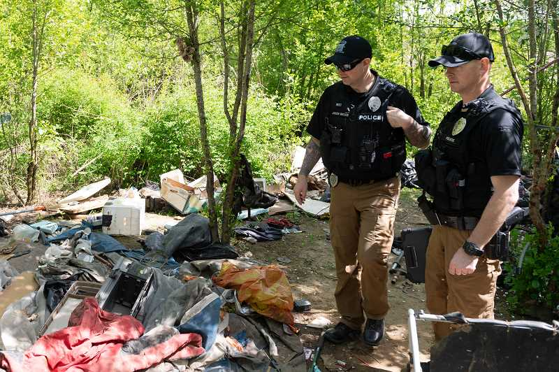 PMG PHOTO: CHRISTOPHER OERTELL - Hillsboro police officers Jason Becker, left, and Mike Abshier check out trash left behind at a homeless camp south of Dairy Creek Park in Hillsboro. The pair are working to form relationships with as many area homeless as possible.