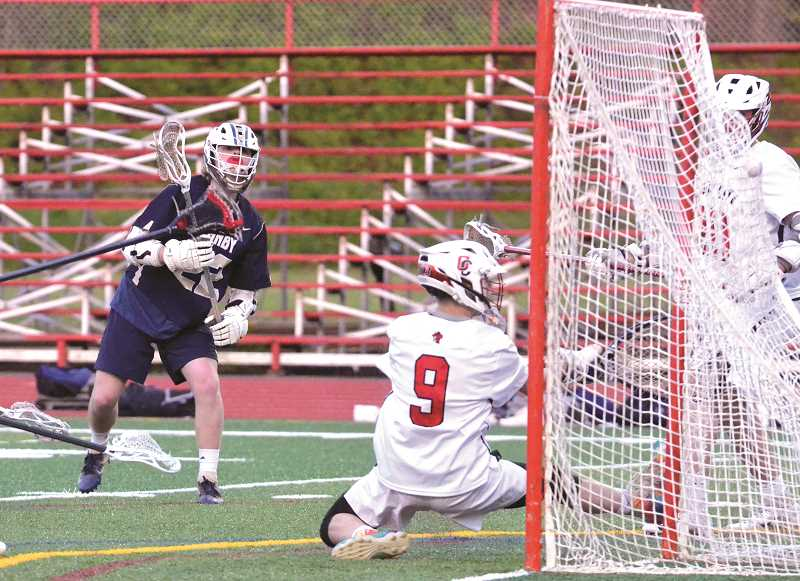 PMG PHOTO: TANNER RUSS - Canby's Jake Kahut scores on the Oregon City goalie.