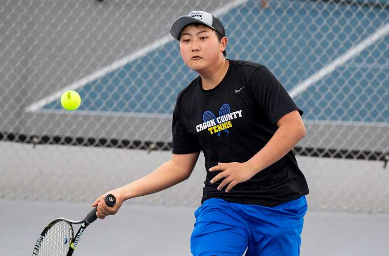 LON AUSTIN/CENTRAL OREGONIAN - Ty Cross plays a shot earlier this year. Cross and his doubles partner Nick Cushman took a 6-3, 6-3 win over their Pendleton counterparts on Friday, helping the Cowboys to a 5-3 dual meet win.