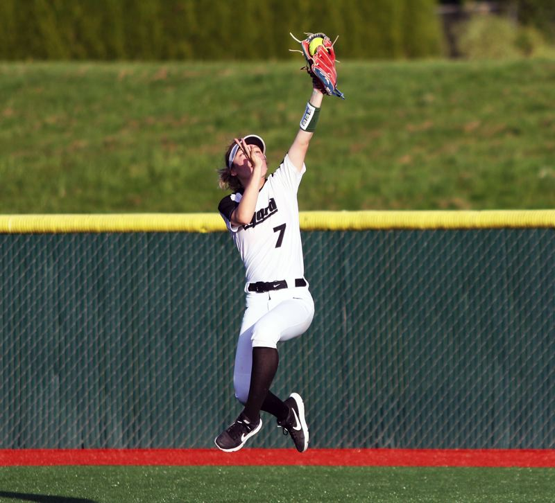PMG PHOTO: DAN BROOD - Tigard High School junior center fielder Lexi Klum makes a spectacular leaping catch in the bottom of the eighth inning in Monday's game at Tualatin.
