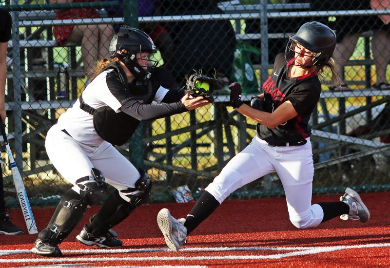 PMG PHOTO: DAN BROOD - Tigard junior catcher Emily Paulson (left) looks to tag out Tualatin senior Andrea Gomez on a close play at the plate in the fifth inning of Monday's game.