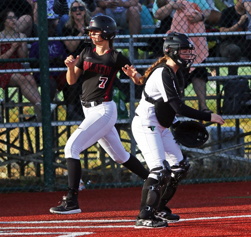 PMG PHOTO: DAN BROOD - Tualatin junior Savannah Braun (left) crosses home plate for a Tualatin fifth-inning run in Monday's Three Rivers League game with Tigard.