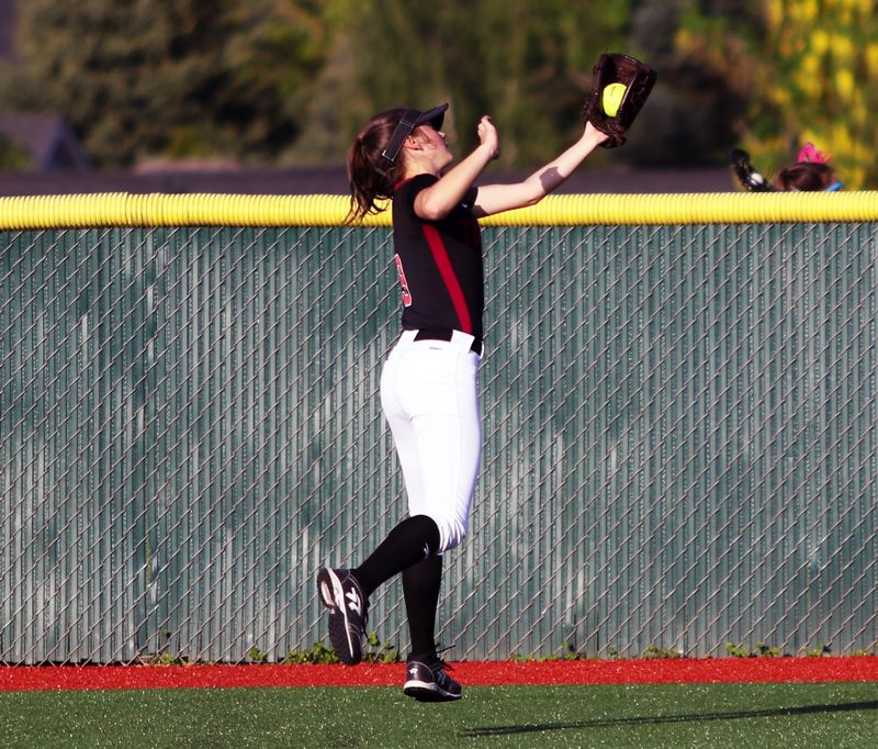 PMG PHOTO: DAN BROOD - Tualatin junior Sydney Wagner makes an over-the-shoulder catch in deep left field during the Wolves' game with Tigard on Monday.