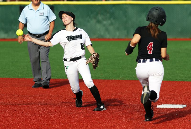PMG PHOTO: DAN BROOD - Tigard senior shortstop Maddie Hoover (left) makes a throw to first base as Tualatin junior Bella Valdes heads to the second base during Monday's game.