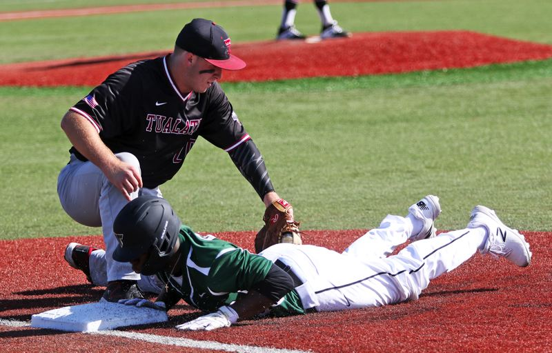 PMG PHOTO: DAN BROOD - Tualatin senior first baseman Gavin Moore (left) puts a tag on Tigard sophomore Josh Schleichardt on a pickoff play during Tuesday's game.