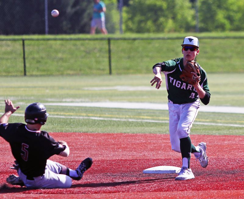 PMG PHOTO: DAN BROOD - Tigard junior shortstop Ethan Clark (right) makes a throw to first base to complete a double play as Tualatin senior Kyle Dernedde slides to second base.
