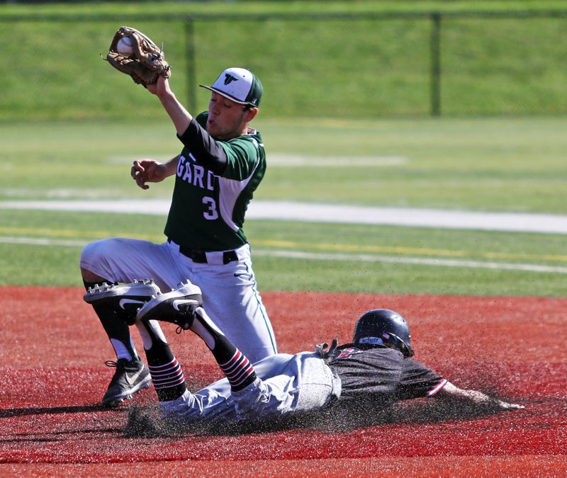 PMG PHOTO: DAN BROOD - Tigard High School senior second baseman Lance Kreisberg (left) grabs the ball as Tualatin senior Cameron Atkinson sides safely to the bag for a stolen base.