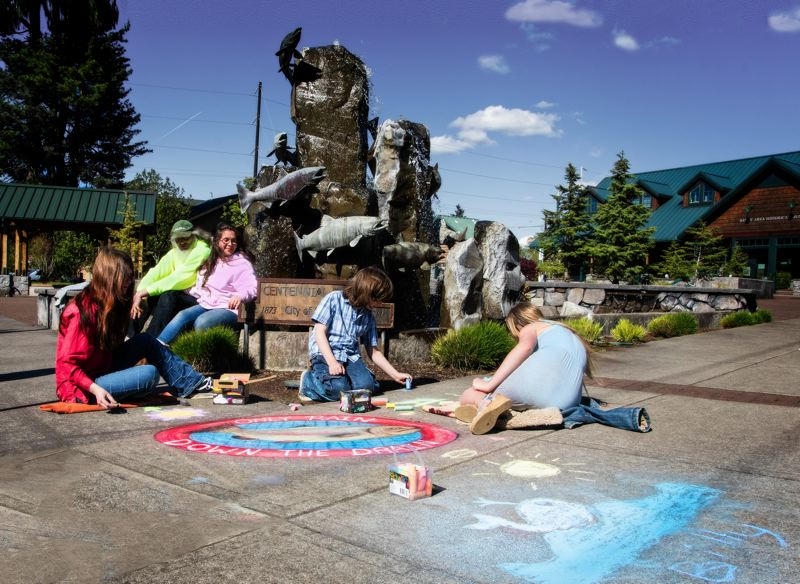 CONTRIBUTED PHOTO: ROD STROH - The Justin and Hope Snyder family, and arts commissioner Beckly Hawley, gave a preview of some 'only rain down the drain' inspired chalk art this past weekend in Centennial Plaza.