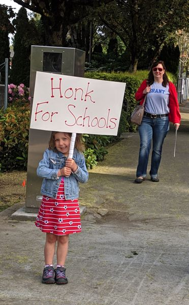 PMG PHOTO: COURTNEY VAUGHN - A child holds a sign near Cleveland High School.