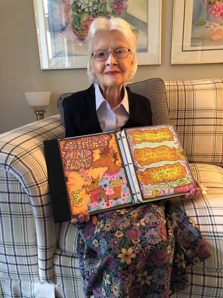 PMG PHOTO: BARB RANDALL  - Marianne Dikeman holds one of more than a dozen binders filled with her son Bill Dikemans original cartoons. She wants to share the colorful art with others.