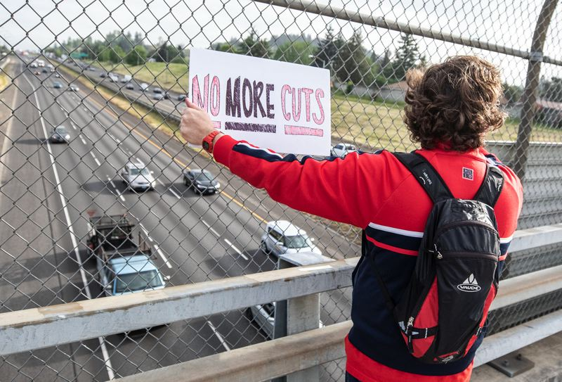PMG PHOTO: JONATHAN HOUSE - Gilbert Park Elementary teacher Lincoln Fisher holds up a sign during Oregon's Teacher Walkout Day.