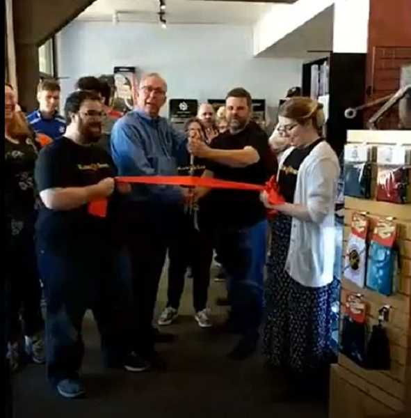 COURTESY PHOTO - Hillsboro mayor Steve Callaway, center, helps cut the ribbon on the newly expanded Rune & Board store on Washington Street.