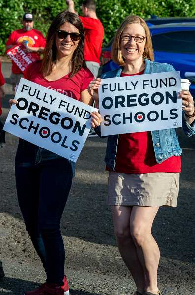 PMG PHOTO: CLARA HOWELL - Noelle Fels, left, and Kelly Fennell, Trillium Creek staff, show their support with signage and by wearing the color red.