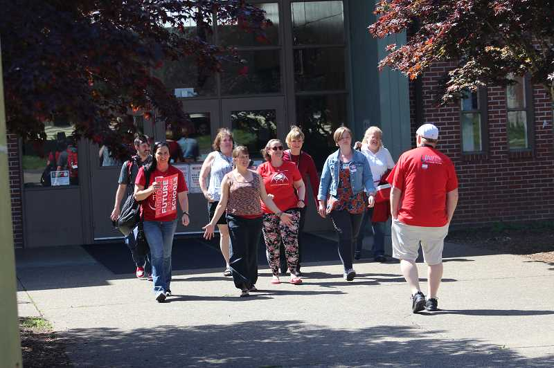 KRISTEN WOHLERS - Molalla River Middle School teachers walk out wearing red in support of better school funding after school on Wednesday, May 8.
