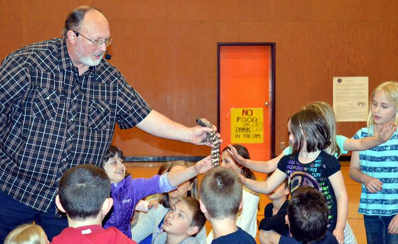 CINDY FAMA - The Reptile Man Richard Ritchey asks who wants to feel the lizard tail.