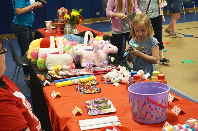 PMG PHOTO: CLAIRE HOLLEY - Miranda Rohrbeck enjoys a cupcake while surveying the table of prizes.