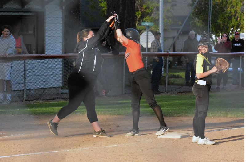 PMG PHOTO: MATT SINGLEDECKER - Scappoose senior Sara Mills and coach Catherine Baggett celebrate Mills' game-winning, two-run triple against St. Helens.