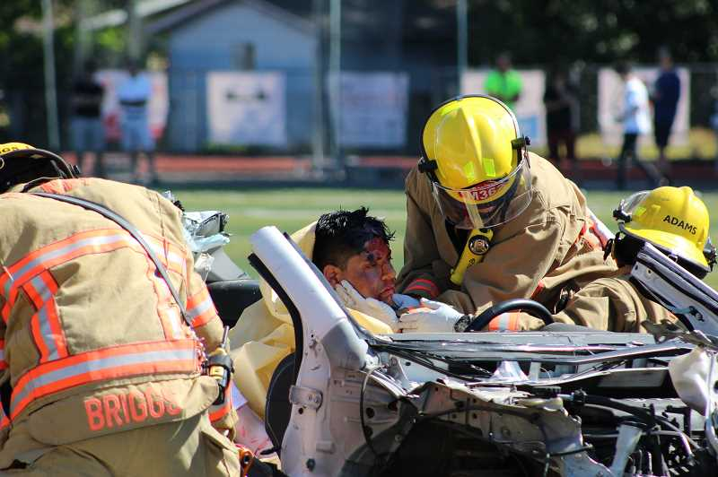 KRISTEN WOHLERS - Paramedics work the scene of the mock car crash at Canby High School on May 9.
