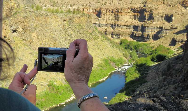 PHOTO BY TOM IRACI - A hiker takes a photo from above the Middle Deschutes River during a previous Scout Camp Rim Photography Hike. The next photography hike will be Monday, May 20, guided by Tom Iraci.