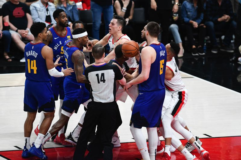 PMG PHOTO: CHRISTOPHER OERTELL - Plaers, including Denver's Will Barton (5) and the Blazers' Zach Collins exchange words in a second-half tussle.